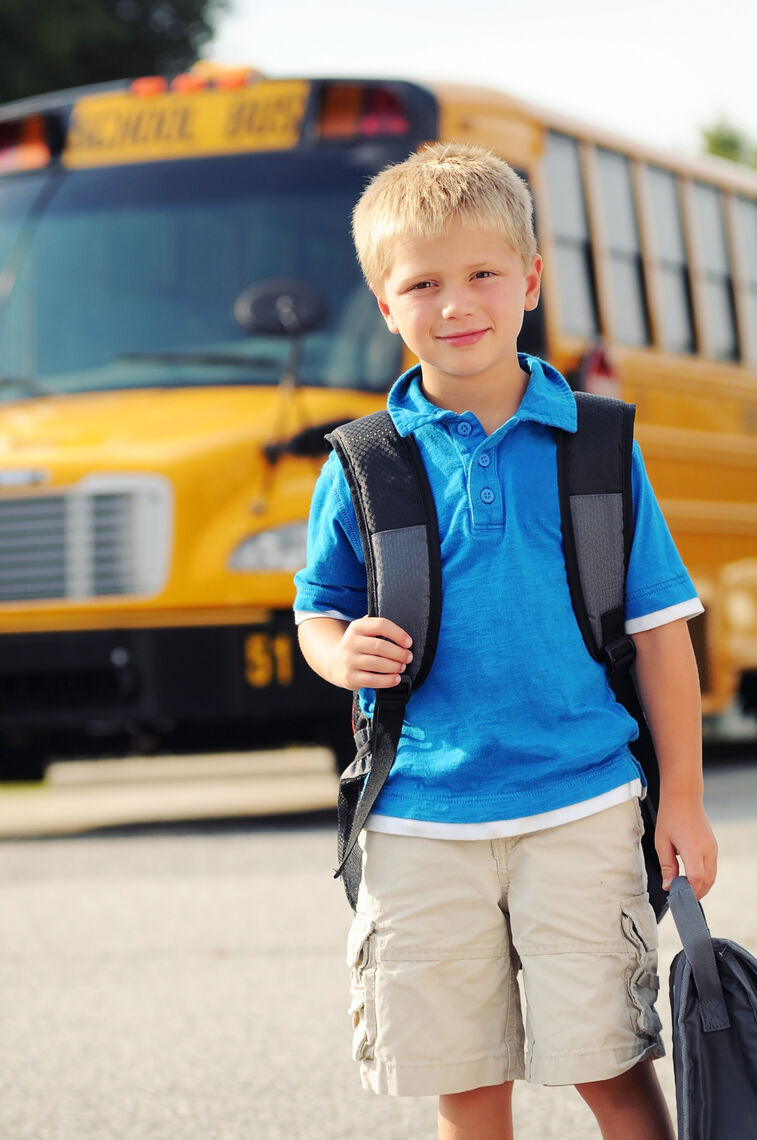 child in front of bus picture